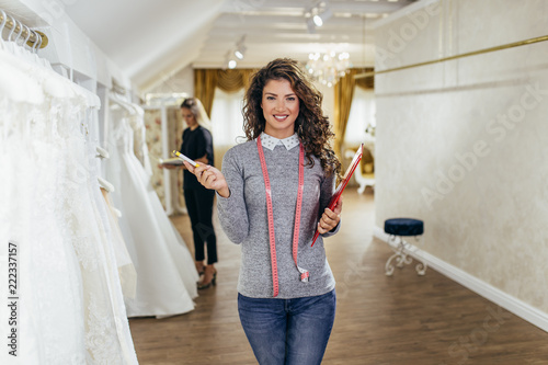 Beautiful young female worker in a modern bridal salon. Fototapete