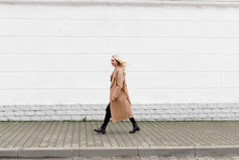 Beautiful Young Stylish Blonde Woman Wearing Long Beige Coat, Black Boots And Black Jeans Walking Through The City Streets. Trendy Casual Outfit. Street Fashion.
