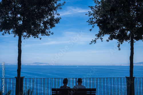 Fotografia  couple in love and relationship sitting on a bench looking at the sea and coastline