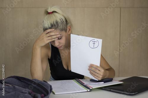Foto  Sad student checking a failed exam