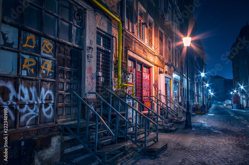 Beautiful old alley with old buildings shot in the night well illuminated by street lamps