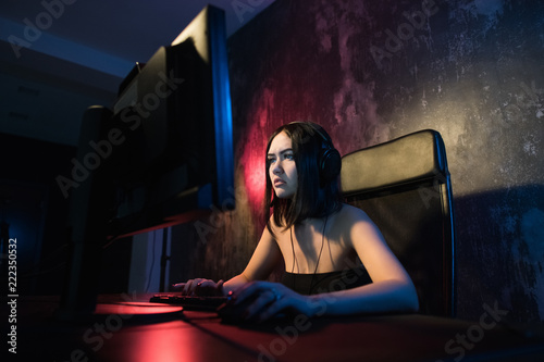 Portrait Shot of a Smiling Beautiful Professional Gamer Girl Playing in First-Person Shooter Online Video Game on Her Personal Computer Canvas Print