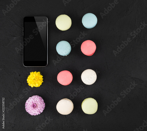 Staande foto Macarons Composition with colorful macarons, flowers and mobile phone on black stone table. Top view, flat lay