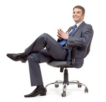 Businessman Sitting On Office Chair With Crossed Legs