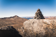 A Large Cairn Marking A Trail In Colorado With Mountains In The Background.