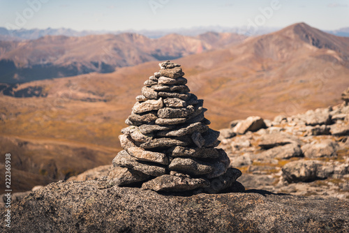 Leinwand Poster A large cairn marking a trail in Colorado with mountains in the background