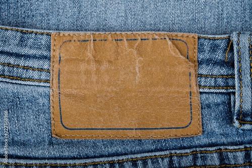 Fotografia  Blank Leather Jeans Label Sewed on a Blue Jeans