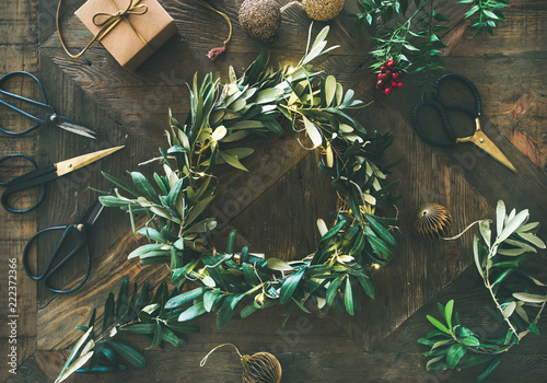 Tuinposter Olijfboom Getting ready for Christmas. Flat-lay of green olive branch festive wreath, Christmas tree decoration toys, gift box and scissors over rustic wood table background, top view, horizontal composition