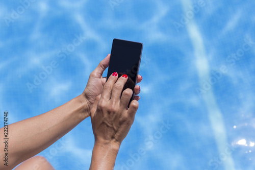 Fotografie, Obraz  woman hands using mobile phone at the pool