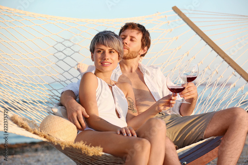 Poster Artist KB Young couple resting with glasses of wine in hammock on beach