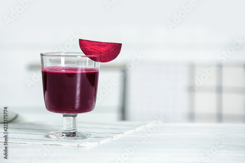 Glass of tasty beet smoothie on table with space for text