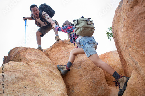 Fotografía  Team of climbers man and woman help each other on top of mountain, climbing hik