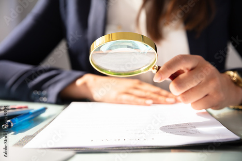 Canvas Print Businesswoman Looking At Contract Form Through Magnifying Glass