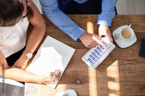 Fotografie, Obraz  Two Businesspeople Using Calendar On Digital Tablet