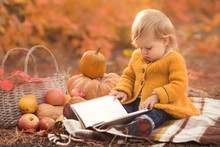 Little Girl Reading Her First Book At Autumn Park