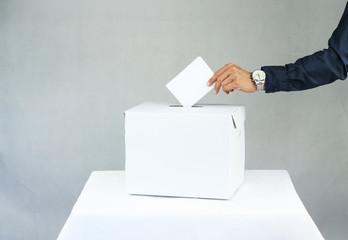 Mężczyzna oddający głos do urny wyborczej