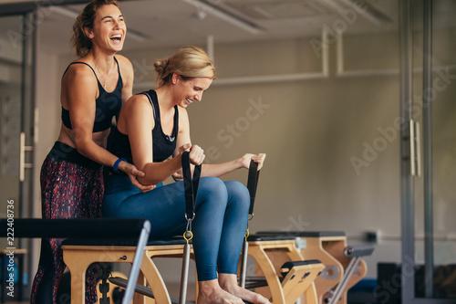 Fototapeta Women laughing while doing pilates workout at a gym obraz