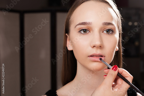 Fotografie, Obraz  makeup artist applying a lip gloss on lips of a young pretty girl