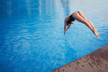 Young Cute Woman In A Black Swimsuit And Long Hair Jumps Into A Pool With Blue Water.
