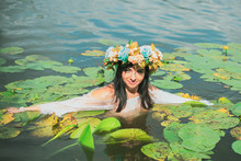 Beautiful Dark Haired Girl In White Dress Posing In River With Water Lilies. Fairytale Story About Modern Ophelia