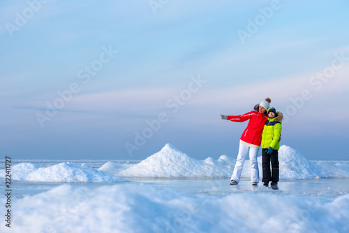 Obraz na plátně  Young mother and her son on icy beach
