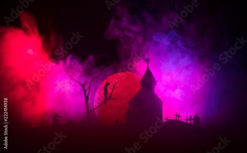 Fotografie, Obraz  Scary view of zombies at cemetery dead tree, moon, church and spooky cloudy sky with fog, Horror Halloween concept