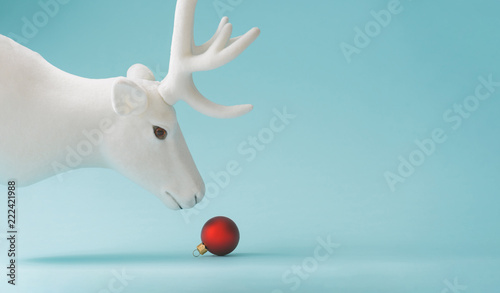 White reindeer with red Christmas bauble decoration on pastel blue background. New Year minimal concept.