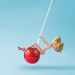 Leinwanddruck Bild - Girl doll swinging on red Christmas bauble decoration. Wrecking ball concept. New Year inspiration.