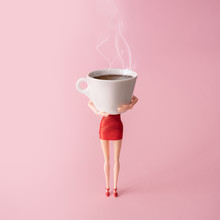 Girl In Red Dress Holding Big Steaming Cup Of Coffee Against Pastel Pink Background. Minimal Coffee Adiction Concept. Poster Advertisement