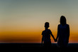 silhouette mother and young boy holding hands at sunset. Space for text