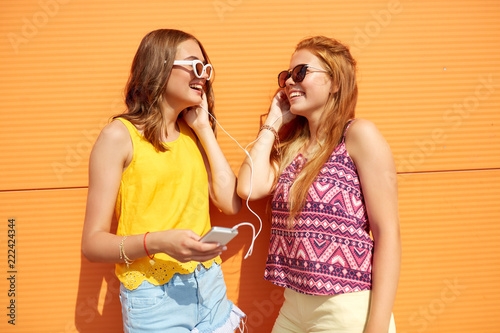 Fototapeta summer, leisure and technology concept - smiling teenage girls in sunglasses and earphones listening to music from smartphone outdoors obraz na płótnie