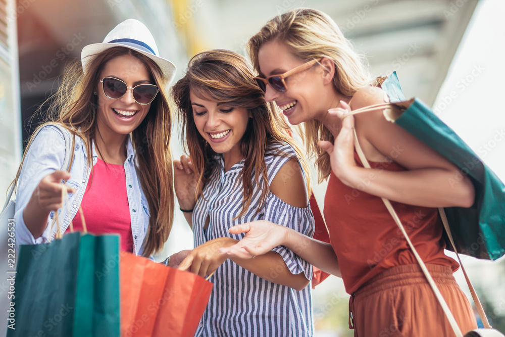 Fototapeta sale, shopping, tourism and happy people concept - beautiful woman with shopping bags in the ctiy