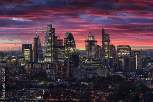 Die beleuchtete City von London nach Sonnenuntergang am Abend mit rotem Himmel und Wolken, Großbritannien