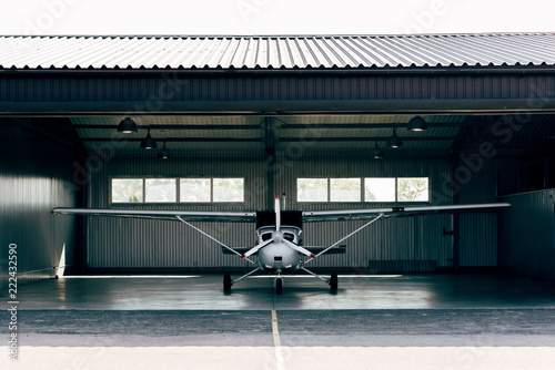 Fototapeta small modern white airplane standing in hangar obraz