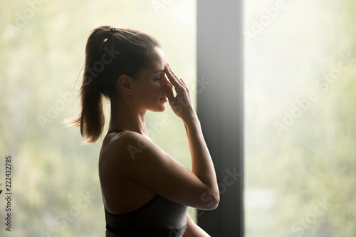 Young sporty woman practicing yoga, doing Alternate Nostril Breathing exercise, nadi shodhana pranayama pose, working out, wearing sportswear, grey top, indoor close up, yoga studio, side view