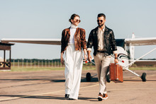 Happy Young Couple In Leather Jackets And Sunglasses Walking With Retro Suitcase Near Airplane
