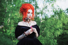 Dark Carnival Attire. Witch Woman With Pale Skin And Red Hair In Black Victorian Gown And Renaissance Bracelet On Hand. Pale Girl Witch With Red Lips. Gothic Look. Victorian Outfit For Carnival.