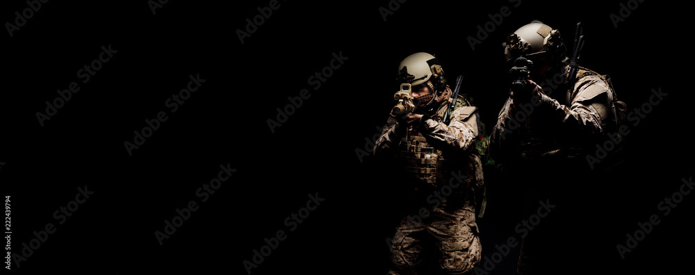 Fototapeta soldiers or private military contractors holding rifle. Image on a black background. war, army, weapon, technology and people concept