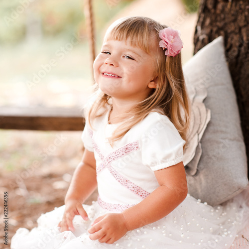 b8a572722b9e Smiling blonde baby girl 1-2 year old wearing white stylish dress outdoors.  Happiness