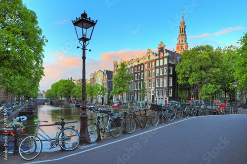 Amsterdam cityscape at sunset with a street lantern at the famous Kloveniersburgwal canal and the Southern Church in the Netherlands