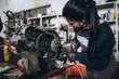 Strong and worthy woman doing hard job in car and motorcycle repair shop.