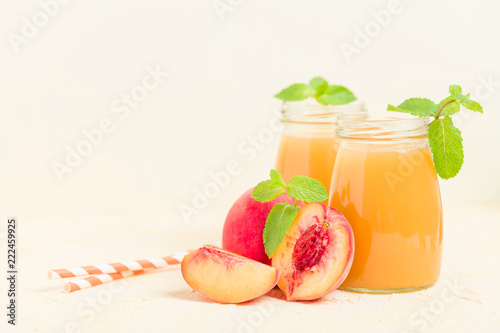 Peach smoothie in glass jars with fresh ripe fruits and green mint leaves on yellow pastel background.