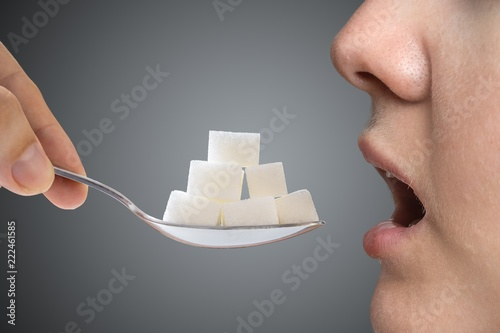 Obraz na plátně  Woman addicted on sugar is eating spoon full of sugar blocks
