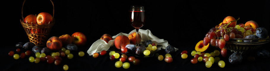 Fototapeta Owoce Large-format panorama with a glass of wine and fruit on a dark background