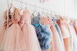 canvas print picture - Beautiful dressy lush pink and blue dresses for girls on hangers at the background of white wall. Kids dresses with feathers for prom and holiday.