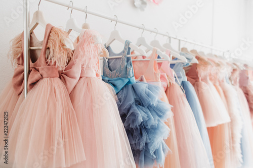 Beautiful dressy lush pink and blue dresses for girls on hangers at the background of white wall Fototapete