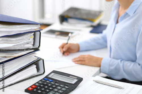 Fotografía  Calculator and binders with papers are waiting to be processed by business woman or bookkeeper back in blur
