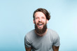 Leinwanddruck Bild happiness enjoyment and laugh. man with a wide grin. portrait of a young bearded hipster guy on blue background. emotion facial expression. feelings and people reaction.