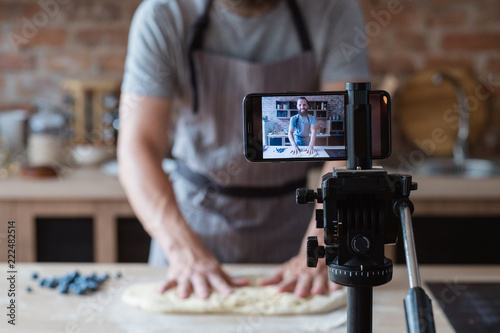 Obraz baker online courses. food preparing and culinary training class concept. smiling bearded chef kneading dough in the kitchen and shooting video of himself using mobile phone on a tripod. - fototapety do salonu