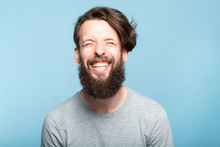 Happiness Enjoyment And Laugh. Exhilarated Man With A Wide Grin. Portrait Of A Young Bearded Hipster Guy On Blue Background. Emotion Facial Expression. Feelings And People Reaction.